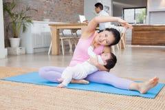 Fille heureuse de mère et de bébé s'exerçant sur le tapis photos stock