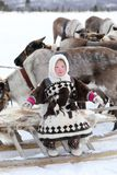 Fille heureuse de Nenets dans des vêtements nationaux parmi le domesti du nord Images libres de droits