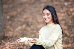 Fille heureuse de sourire de belle femme asiatique et v?tements chauds de port hiver et portrait d'automne ? ext?rieur en parc photographie stock