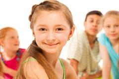 Fille heureuse de sourire d'école avec des amis sur le dos Images libres de droits