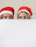 Fille heureuse de Tho dans le chapeau de Santa se cachant derrière une bannière vide vide W Image stock