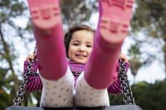 Fille heureuse de trois ans ayant l'amusement sur une oscillation Image stock