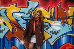 Fille heureuse devant un mur de graffiti Photos stock