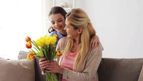 Fille heureuse donnant des fleurs pour enfanter à la maison clips vidéos