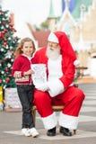 Fille heureuse donnant la lettre à Santa Claus Photographie stock