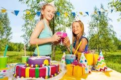 Fille heureuse donnant le cadeau d'anniversaire à son ami Photographie stock libre de droits