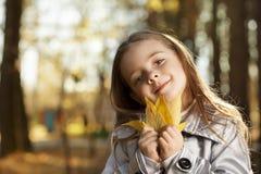 Fille heureuse en automne de feuilles photo stock