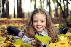 Fille heureuse en automne de feuilles photos stock