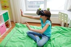 Fille heureuse en casque de vr ou verres 3d à la maison Image libre de droits
