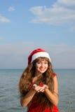 Fille heureuse et belle Santa Claus sur la plage Photo stock