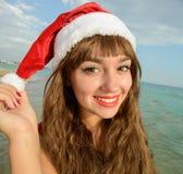 Fille heureuse et belle Santa Claus sur la plage Image stock
