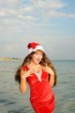 Fille heureuse et belle Santa Claus sur la plage Image libre de droits