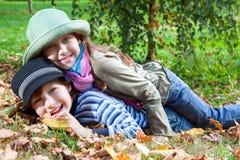 Fille heureuse et garçon appréciant l'automne d'or Photographie stock libre de droits