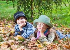 Fille heureuse et garçon appréciant l'automne d'or Photos libres de droits