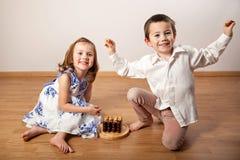 Fille heureuse et garçon jouant un jeu de société photos stock