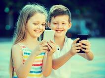 Fille heureuse et garçon regardant des téléphones portables en parc Images stock