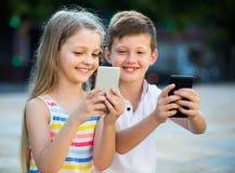 Fille heureuse et garçon regardant des téléphones portables en parc Photographie stock