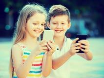 Fille heureuse et garçon regardant des téléphones portables en parc Image libre de droits