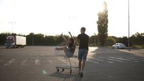 Fille heureuse et jeune avec les mains augmentées se reposant dans un caddie Son ami masculin pousse le chariot Style de vie heur banque de vidéos