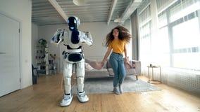 Fille heureuse et une danse de robot ensemble dans une chambre Robot, cyborg et concept humain banque de vidéos