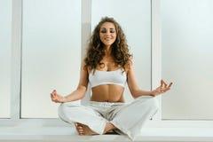 Fille heureuse faisant le yoga sur un tir de filon-couche de fenêtre Images stock