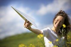 Fille heureuse jouant avec l'avion de papier Photographie stock libre de droits