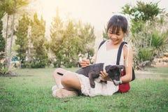 Fille heureuse jouant avec le petit chien à l'arrière-plan de nature Photos libres de droits