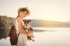Fille heureuse jouant avec le petit chien à l'arrière-plan de nature Photos stock