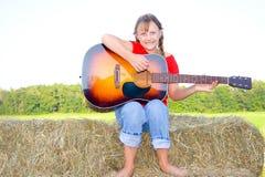 Fille heureuse jouant la guitare sur une balle de paille. Photo stock