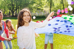 Fille heureuse jouant le parachute coloré en parc Images libres de droits