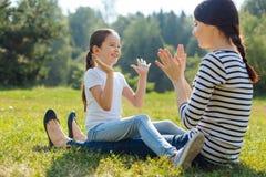 Fille heureuse jouant le Pat-un-gâteau avec sa mère dehors Images libres de droits