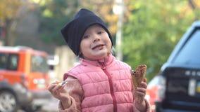 Fille heureuse mangeant la crème glacée de chocolat avec un cône de gaufre, dessert délicieux banque de vidéos