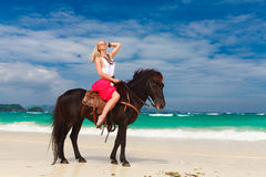 Fille heureuse marchant avec le cheval sur une plage tropicale Photos libres de droits