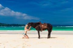 Fille heureuse marchant avec le cheval sur une plage tropicale Photographie stock libre de droits