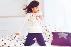 Fille heureuse mignonne chantant dans la brosse de microphone dans la lumière du soleil de matin à la maison Image libre de droits