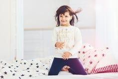 Fille heureuse mignonne chantant dans la chambre à coucher dans la lumière du soleil de matin Image stock