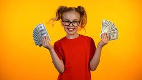 Fille heureuse mignonne montrant des groupes d'argent liquide du dollar, concession de gain de wunderkind, revenu photos libres de droits