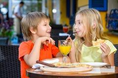 Fille heureuse ou satisfaisante de largeur de garçon mangeant de la pizza et Photo stock