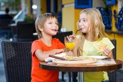 Fille heureuse ou satisfaisante de largeur de garçon mangeant de la pizza et Images stock