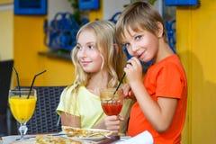 Fille heureuse ou satisfaisante de largeur de garçon mangeant de la pizza et Photos stock