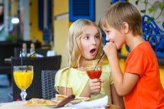 Fille heureuse ou satisfaisante de largeur de garçon mangeant de la pizza et Photographie stock libre de droits