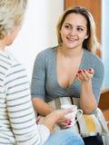 Fille heureuse partageant des bavardages avec la maman mûre tandis que thé-drinkin Image libre de droits