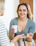 Fille heureuse partageant des bavardages avec la maman mûre tandis que thé-drinkin Photos stock