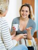 Fille heureuse partageant des bavardages avec la maman mûre tandis que thé-drinkin Photo libre de droits