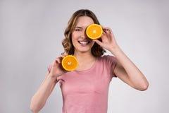 Fille heureuse posant avec le sourire orange d'isolement photos stock