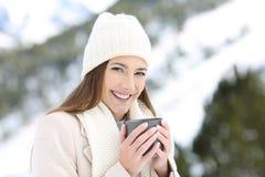 Fille heureuse posant tenant une tasse de café en hiver photos stock