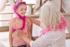 Fille heureuse positive utilisant une écharpe de plume Photographie stock libre de droits