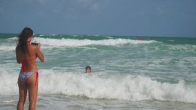 Fille heureuse prenant la photo avec le téléphone portable de son ami sur la plage tropicale en mer tandis qu'ayez les vacances Image stock