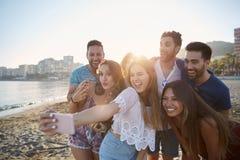 Fille heureuse prenant le selfie avec des amis sur la plage Image stock