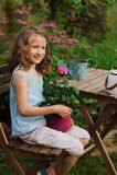 fille heureuse rêveuse d'enfant détendant dans le jardin de soirée d'été avec la fleur de géranium dans le pot Images libres de droits